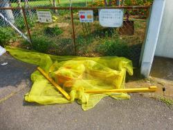 動物を防ぐためのネットに重石を置いている例